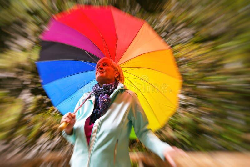 Mitte alterte die graue behaarte Frau, die bunten Regenschirm draußen an einem sonnigen Tag hält stockbild