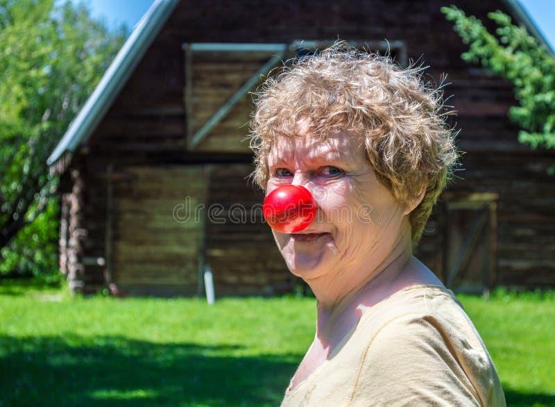 Mitte alterte die kaukasische Frau, die eine rote Nase trägt stockbild