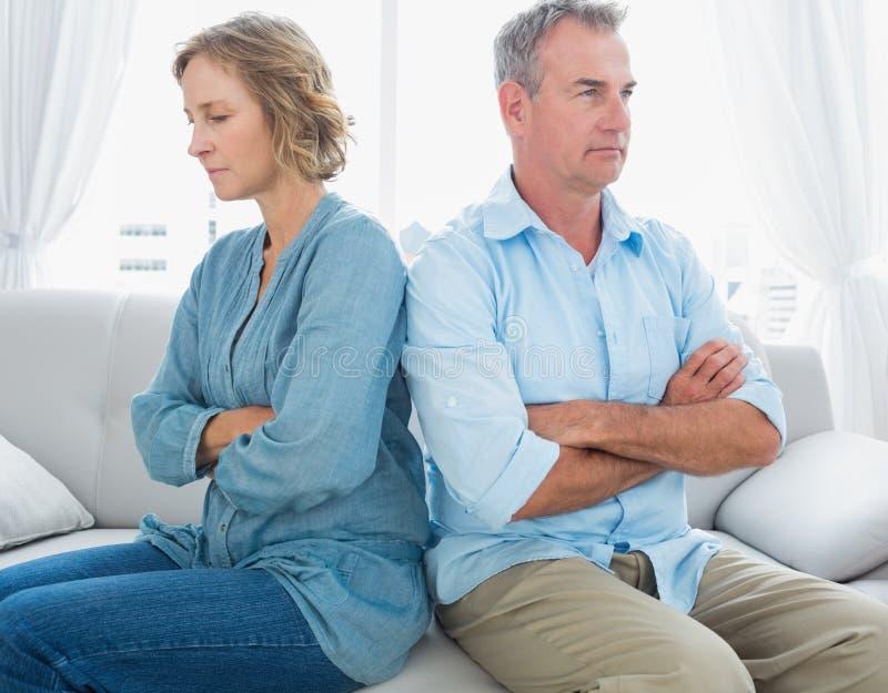 Mitte alterte die Paare, die auf der Couch sitzen, die nicht nach einer Feige spricht lizenzfreie stockbilder