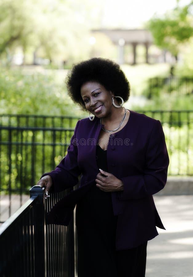 Mitte gealterte Afroamerikaner-Frau draußen parken das lächeln stockfoto
