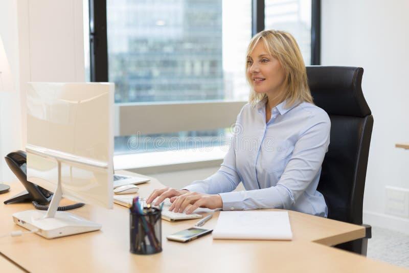Mitte gealterte Geschäftsfrau, die im Büro arbeitet stockfoto