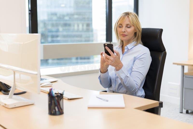Mitte gealterte Geschäftsfrau, die im Büro arbeitet Unter Verwendung Smartphone lizenzfreie stockbilder