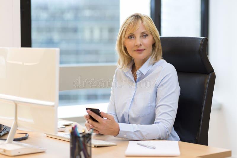 Mitte gealterte Geschäftsfrau, die im Büro arbeitet Unter Verwendung Smartphone lizenzfreies stockfoto