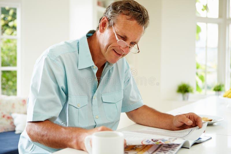 Mitte gealterte Mann-Lesezeitschrift über Frühstück lizenzfreies stockfoto
