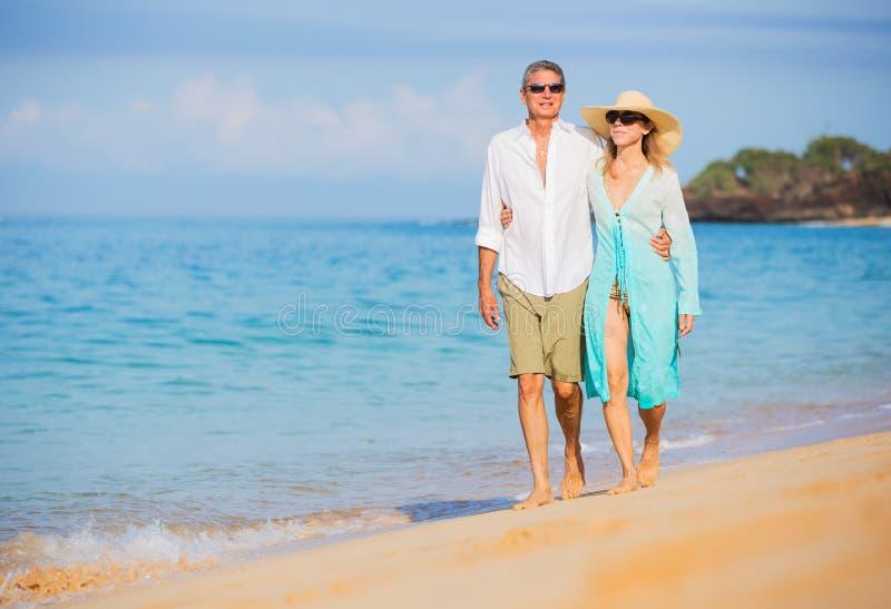 Mitte gealterte Paare, die Weg auf dem Strand genießen lizenzfreies stockbild