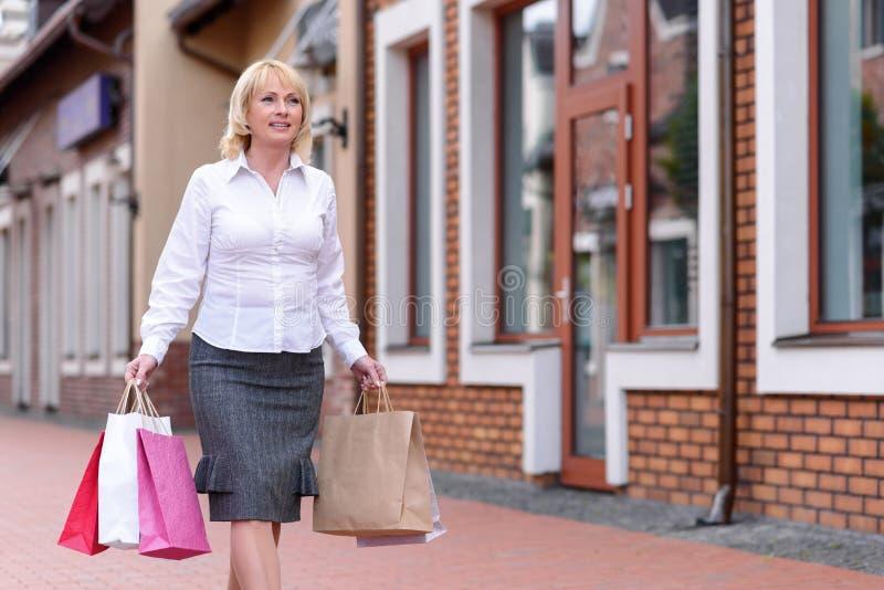 Mitte gealterter gehender Einkauf Dame lizenzfreies stockbild