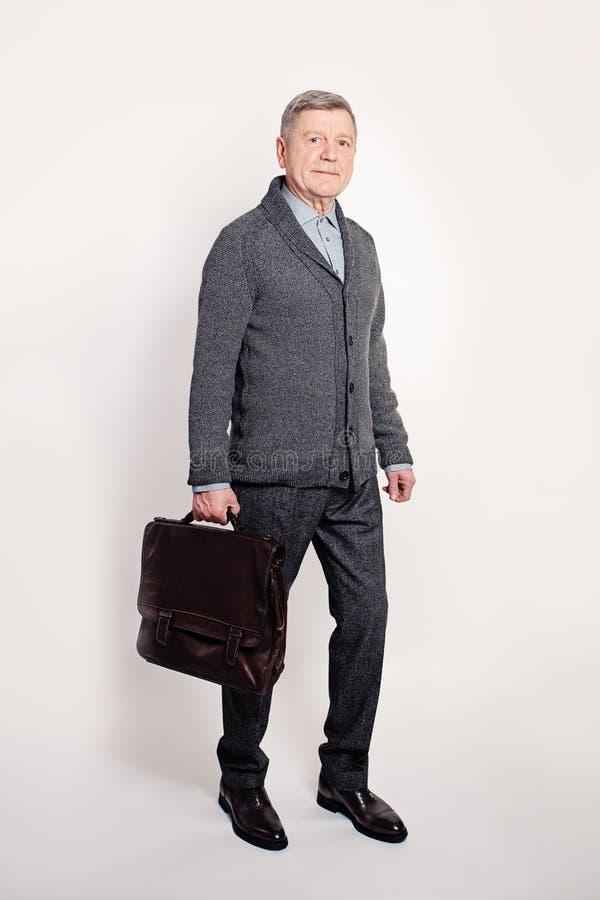 Mitte gealterter Geschäftsmann, der einen Brown-Leder-Aktenkoffer hält lizenzfreie stockbilder