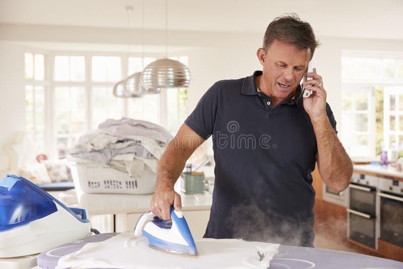 Mitte gealterter Mann telefonisch abgelenkt beim Bügeln lizenzfreie stockfotografie