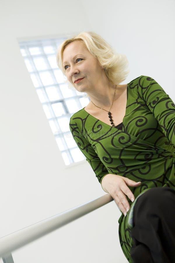 Mitte gealtertes blondes im Grün lizenzfreies stockfoto