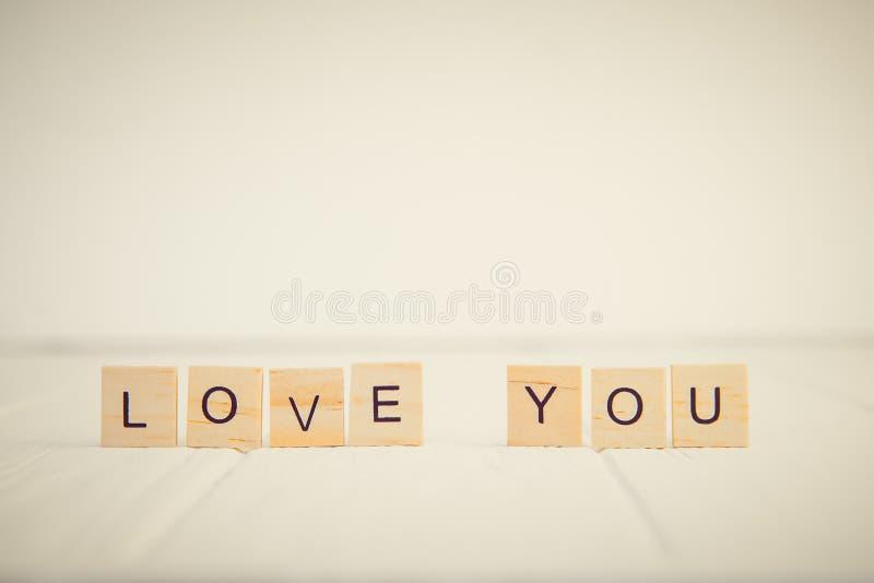 Mitteilung buchstabierte ich liebe dich in den Holzklötzen, die auf weißem Holztisch stehen Rosa Herz zwei Einfachheitskonzept we stockfotografie