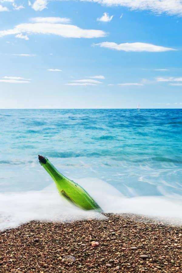 Mitteilung in der Flasche auf Seestrand stockfoto