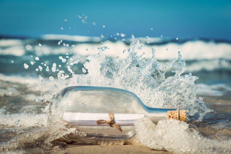 Mitteilung in der Flasche, die mit Welle aus Ozean kommt lizenzfreie stockfotos