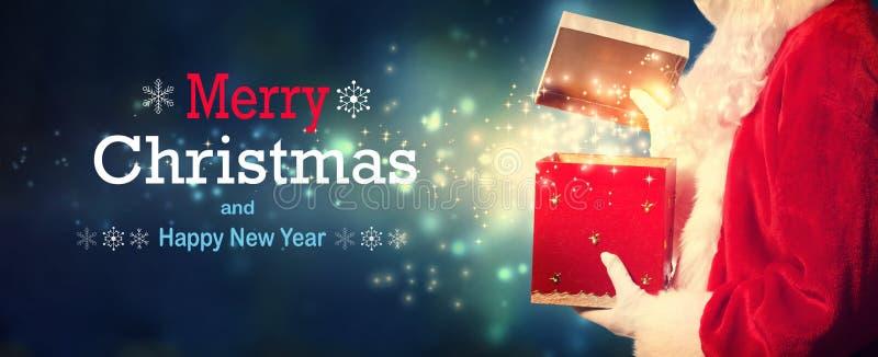 Mitteilung der frohen Weihnachten und des guten Rutsch ins Neue Jahr mit Sankt, die eine Geschenkbox öffnet stockbilder