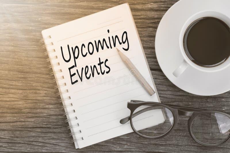 Mitteilung der Konzept-bevorstehenden Veranstaltungen auf Notizbuch mit Gläsern, Bleistift stockbild
