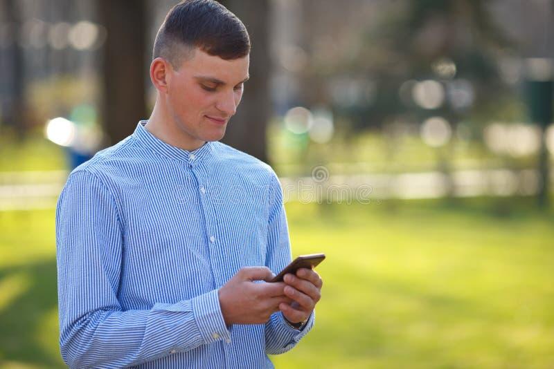 Mitteilung des jungen Mannes Leseam intelligenten Telefon draußen Gespräch, stockfotos