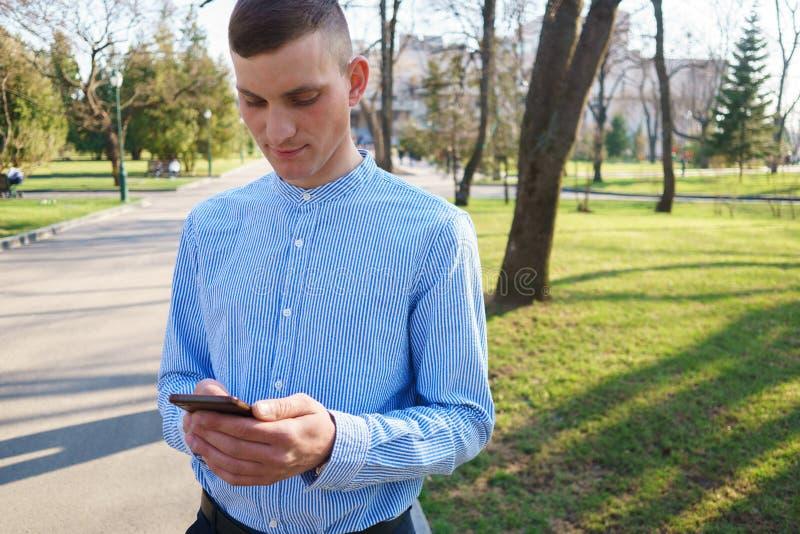 Mitteilung des jungen Mannes Leseauf seinem Mobiltelefon Gespräch, Gerät lizenzfreie stockfotos