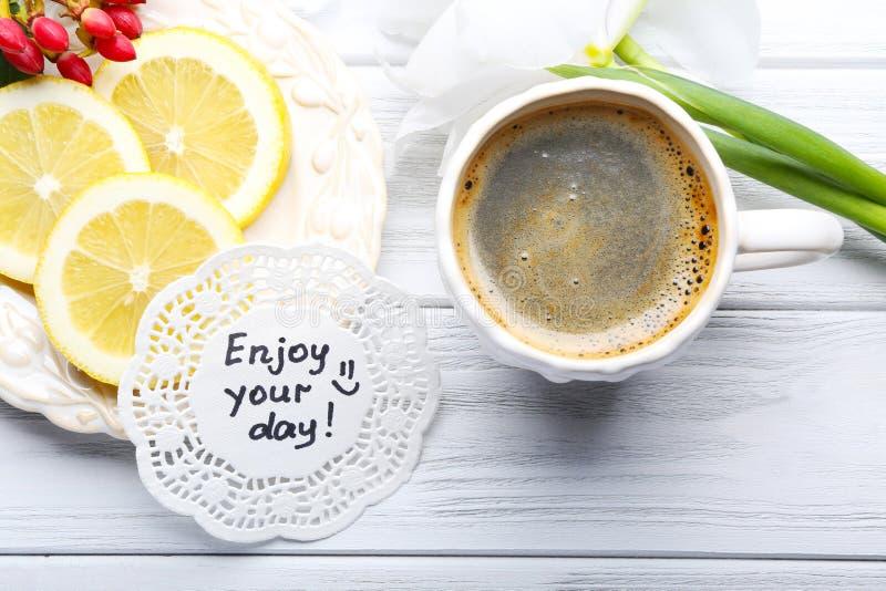 Mitteilung genießen Ihren Tag mit Tasse Kaffee, Zitronenscheiben und Galan stockfoto