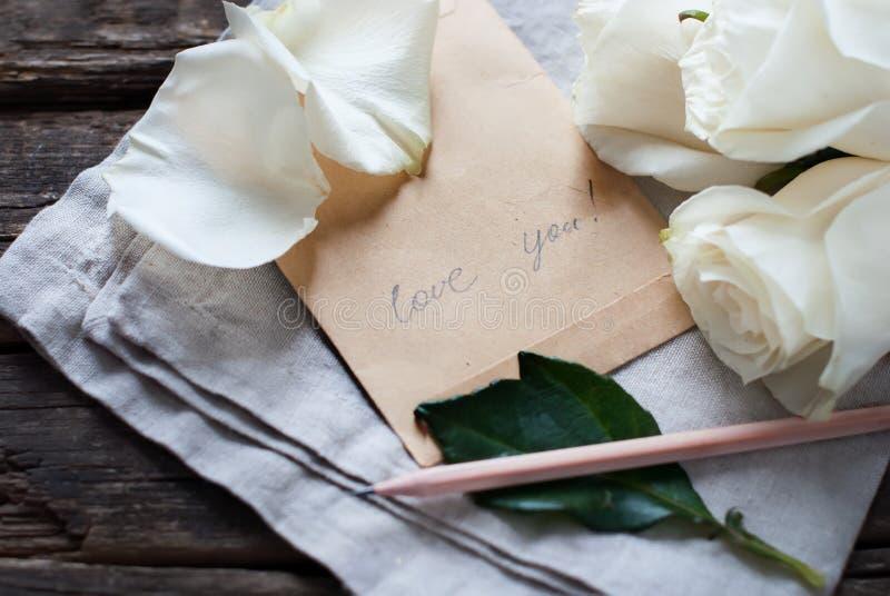 Mitteilungs-Liebe Sie auf Weinlese Buchstaben, Bleistift, weiße Rosen lizenzfreies stockfoto