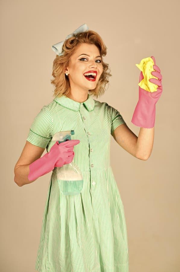 Mittel für das Waschen der Fenster Haushälterin in der Uniform mit sauberem Spray, Staubtuch lizenzfreie stockfotos