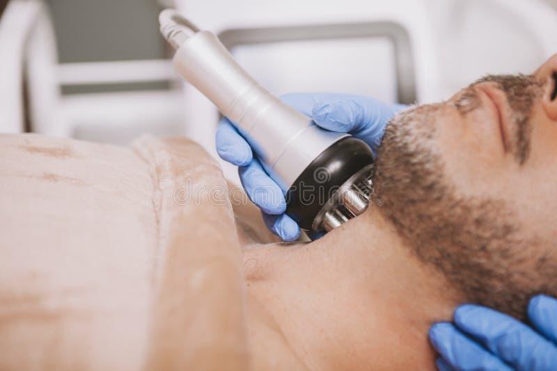 Mittel-gealterter m?nnlicher Kunde, der Hardware Cosmetologybehandlung genie?t lizenzfreies stockbild