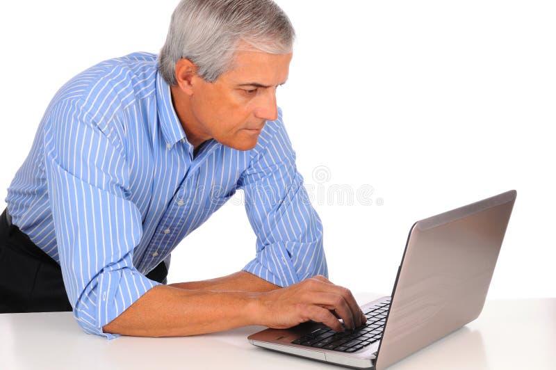 Mittelalter-Geschäftsmann am Schreibtisch mit Laptop stockbilder
