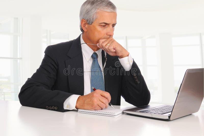 Mittelalter-Geschäftsmann am Schreibtisch mit Laptop lizenzfreies stockfoto