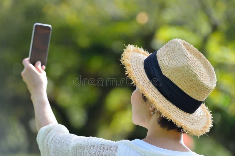 Mittelalterfrau, die ein selfie an ihrem Telefon nimmt lizenzfreie stockbilder
