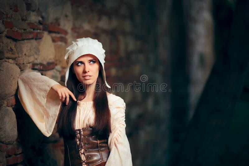 Mittelalterliche Frau in historisches Kostüm-tragendem Korsett-Kleid und Mütze stockfotos