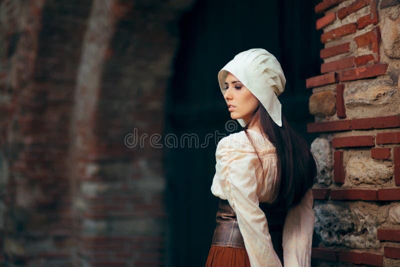 Mittelalterliche Frau in historisches Kostüm-tragendem Korsett-Kleid und Mütze stockbild