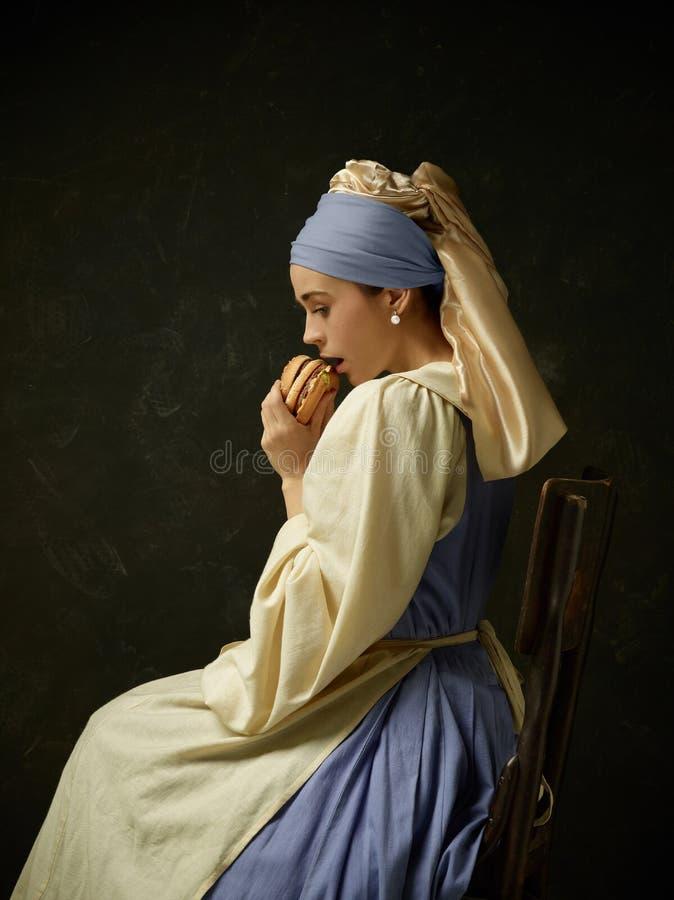 Mittelalterliche Frau in historisches Kostüm-tragendem Korsett-Kleid und Mütze lizenzfreie stockfotografie