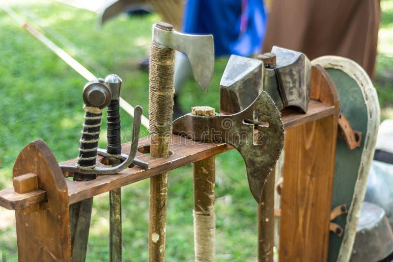 Mittelalterliche Metallaxt und -klinge in einem hölzernen Stand auf dem Festival stockfoto