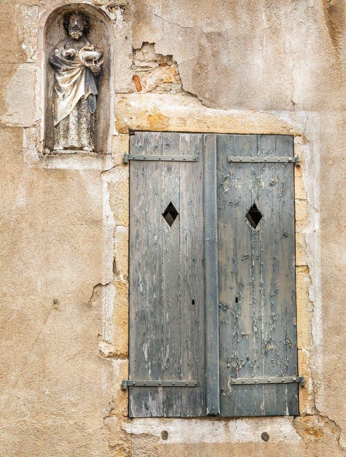Mittelalterliche religiöse Statue in der Wandnische und verwitterte hölzerne Fensterläden in Semur en Auxois, Frankreich lizenzfreie stockbilder