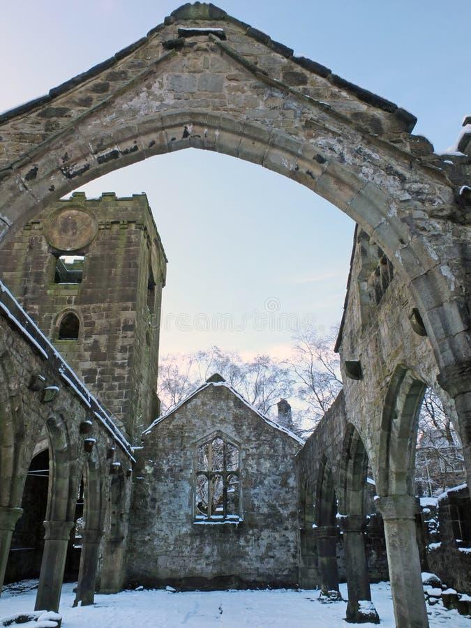 Mittelalterliche ruinierte Kirche im heptonstall umfasst im Schnee, der B?gen und Spalten gegen einen blauen Winterhimmel zeigt lizenzfreie stockbilder