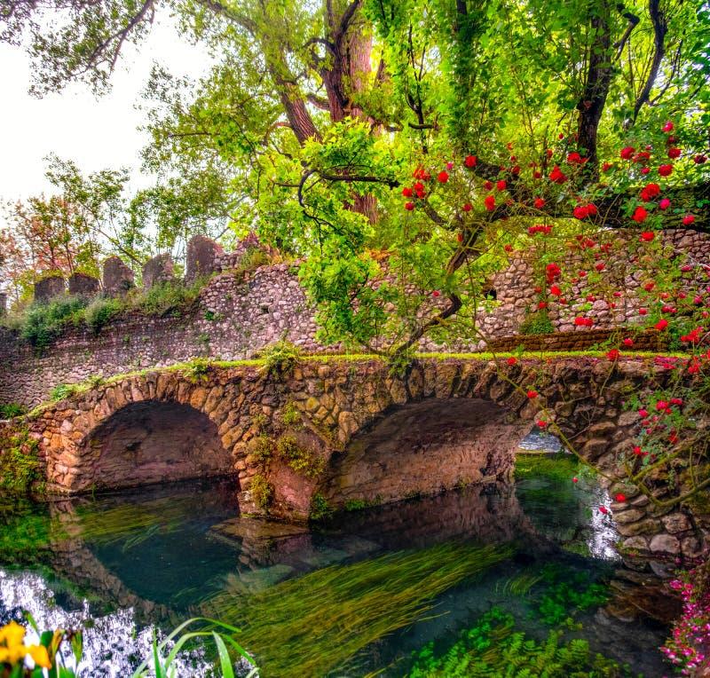 Mittelalterliche Steinbrücke in buntem Garten Edens vibrierend mit Rosen und Fluss stockbild