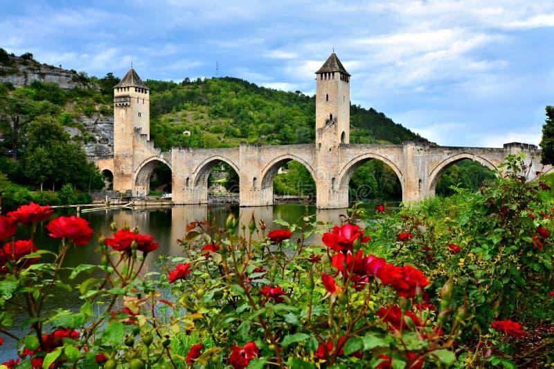 Mittelalterliche Steinbrücke in Cahors, Frankreich mit roten Rosen stockfotografie