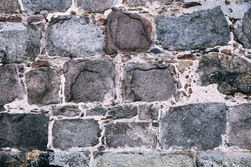 Mittelalterliche Steinwand hergestellt von den alten und großen rechteckigen enormen Steinblöcken als Oberflächenbeschaffenheitsh stockbild