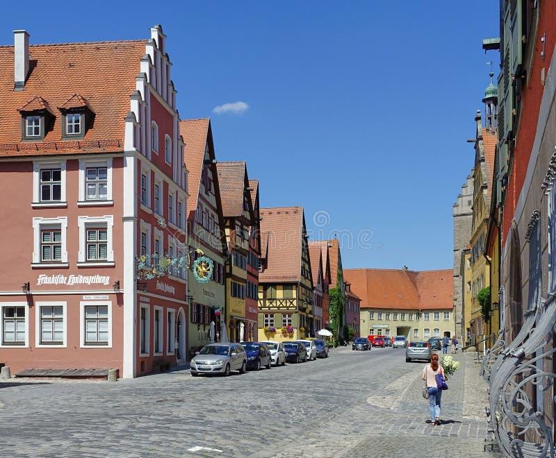 Mittelalterliche Straße mit der Frau, die mit frischen geschnittenen Blumen geht stockbilder