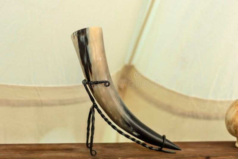 Mittelalterliche Weinschale hergestellt vom Kuhhorn im Metallstand auf einem hölzernen Regal lizenzfreie stockfotos