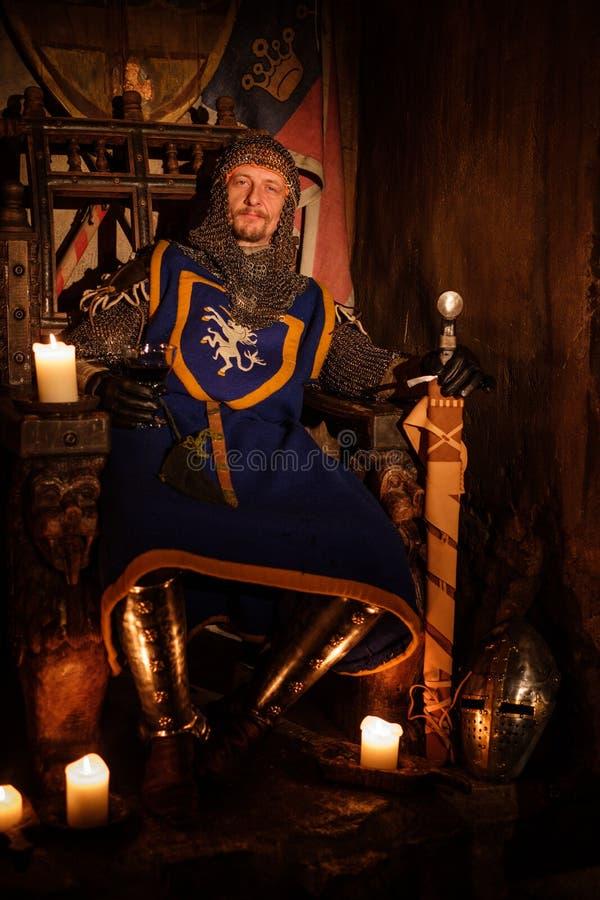 Mittelalterlicher König auf Thron im alten Schlossinnenraum lizenzfreie stockfotos