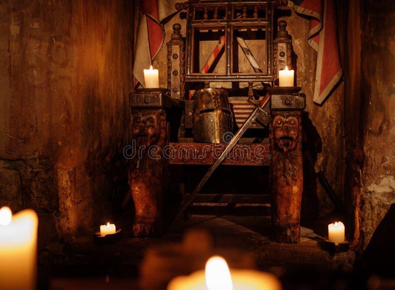 Mittelalterlicher königlicher Thron mit Sturzhelm und Klinge im alten Schlossinnenraum lizenzfreies stockfoto