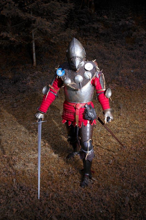 Mittelalterlicher Krieger in der Klage des Ritters, die in dunklem Forest Ready für Kampf, Schuss in voller Länge steht lizenzfreies stockbild