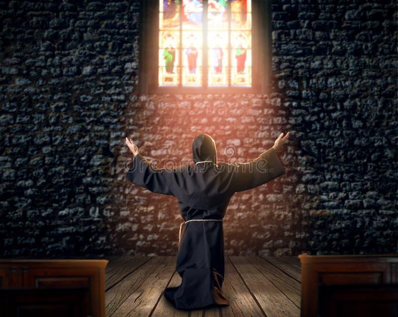 Mittelalterlicher Mönch, der in der Kirche knit und betet stockfotografie