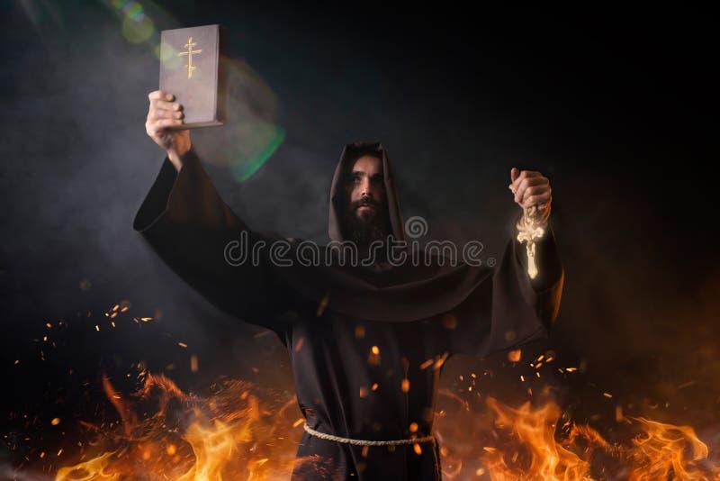 Mittelalterlicher Mönch steht im Feuer mit Buch in den Händen lizenzfreie stockfotos