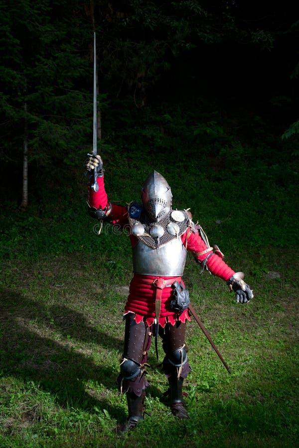 Mittelalterlicher Ritter With Sword in angehobener Hand im Wald nachts stockfotografie