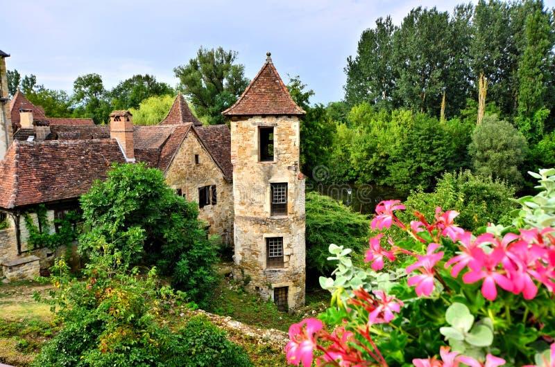 Mittelalterliches Haus und Turm mit Blumen in Carennac, Frankreich stockbilder