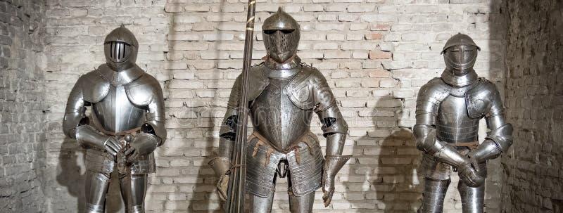 Mittelalterliches Rüstungsritterstahlmetallhorizontales Backsteinmauerbraun stockfotos
