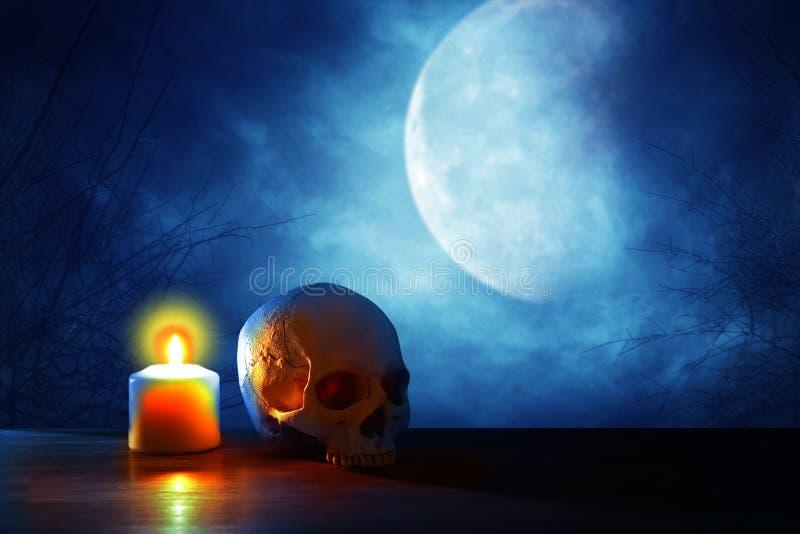 mittelalterliches und Fantasiehalloween-Konzept Menschlicher Schädel, Vollmond und brennende Kerze über altem Holztisch nachts fu lizenzfreie stockfotos