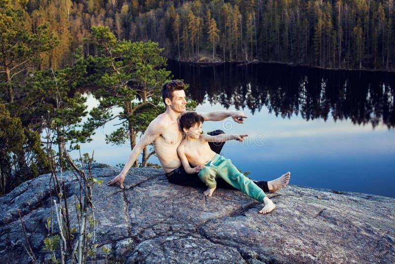 Mittelaltermann mit dem kleinen netten Sohn, der zusammen Sportyoga auf die Oberseite des Berges, glückliche Familienlebensstille stockbild