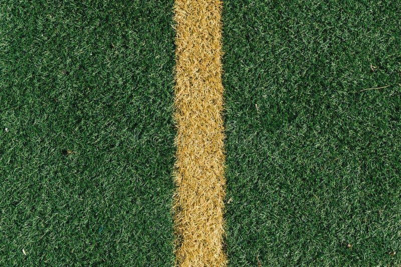 Mittellinie auf Fußballplatz, gelbe Markierung auf künstlichen gras lizenzfreie stockfotos