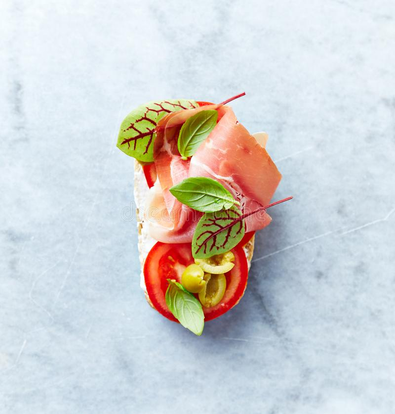 Mittelmeer-Ähnliches offenes Sandwich mit Schinken-, Tomaten-, Gren Olives-, Basilikumblättern Serrano und rotem Sauerampfer stockfoto